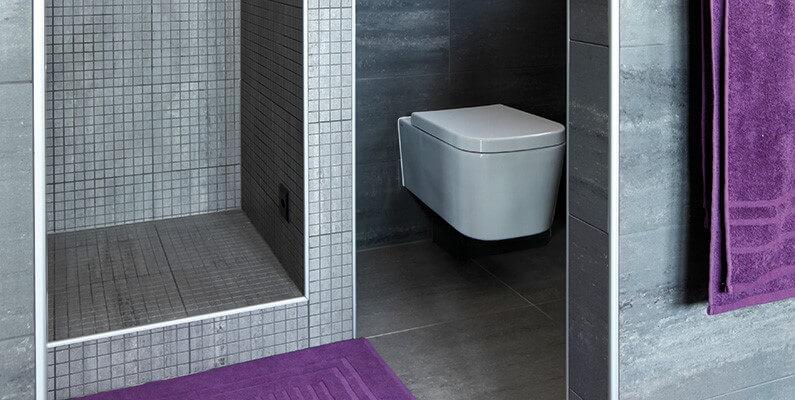 Delno zagrajena WC-školjka v kopalnici.